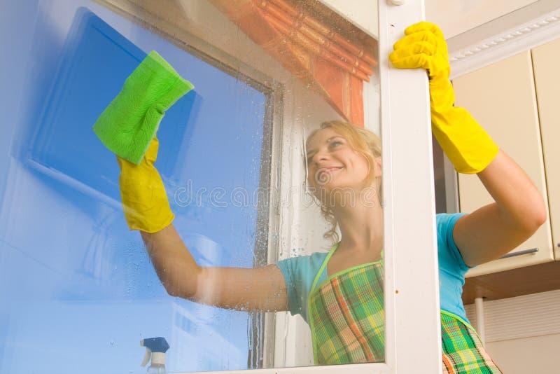 Donna che pulisce una finestra immagini stock libere da diritti