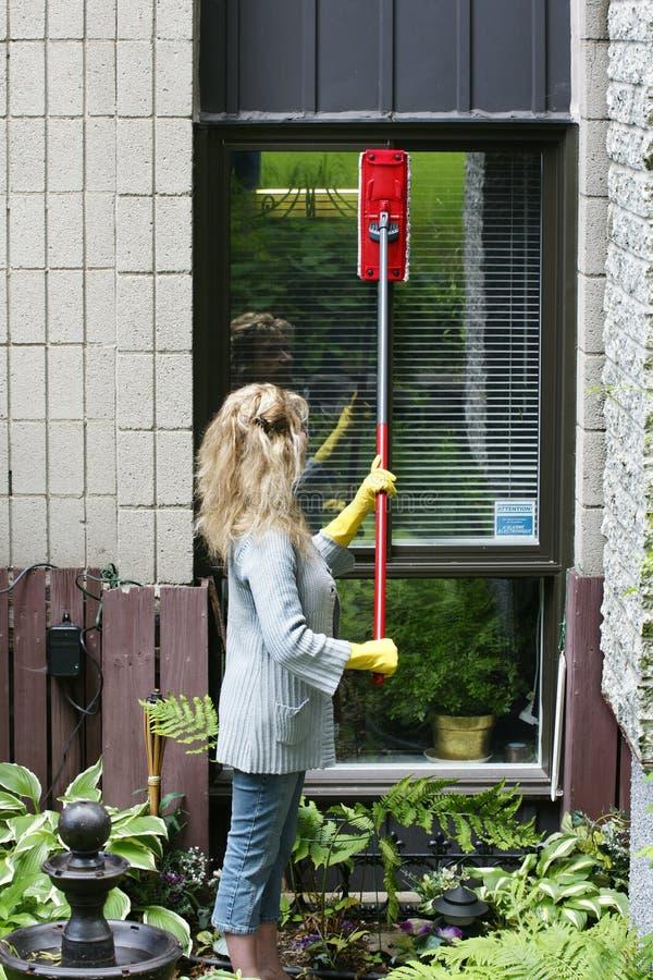 Donna che pulisce una finestra fotografia stock