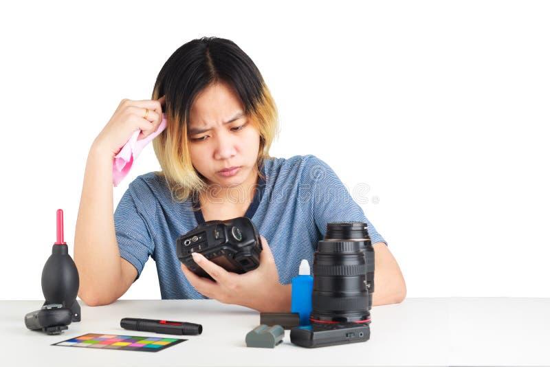Donna che pulisce una macchina fotografica con il panno e l'attrezzatura di fotografia sulla tavola fotografia stock
