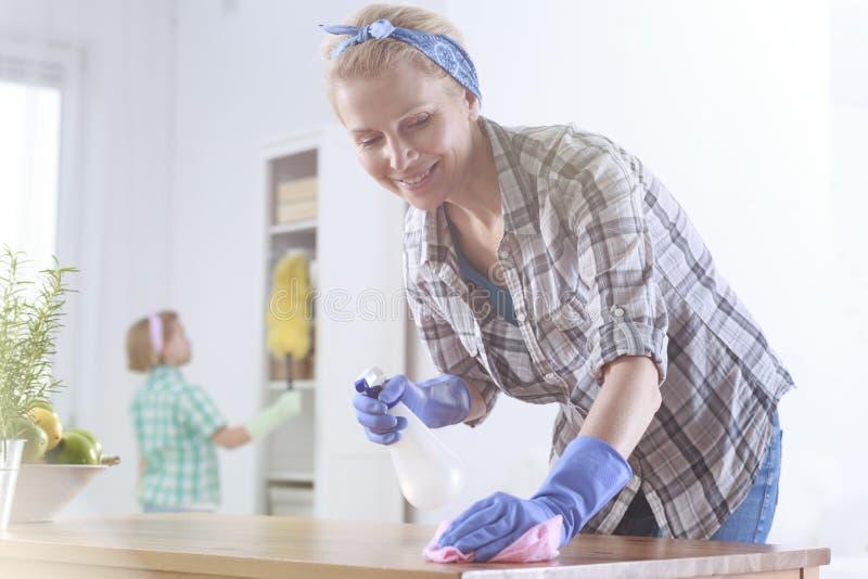 Donna che pulisce una tavola immagini stock libere da diritti