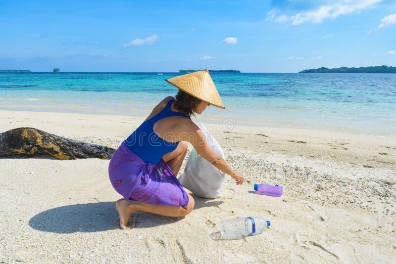 Donna che raccoglie le bottiglie di plastica sulla bella spiaggia tropicale, mare del turchese, giorno soleggiato, riciclante con fotografie stock