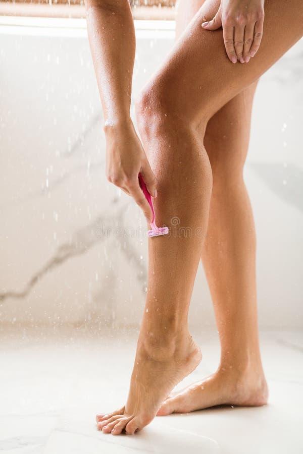 Donna che rade le gambe, prendenti doccia nel giorno di estate caldo fotografia stock libera da diritti