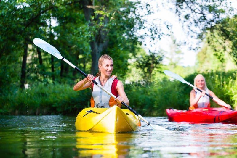 Donna che rema con la canoa sul fiume della foresta fotografia stock