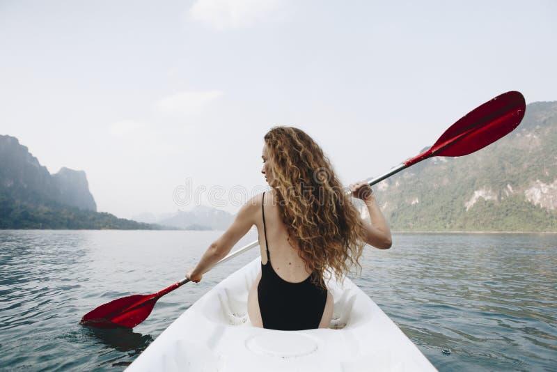 Donna che rema una canoa attraverso un parco nazionale fotografia stock