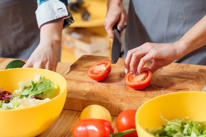 Donna che rende a pomodoro di taglio dell'insalata pasto sano immagini stock libere da diritti