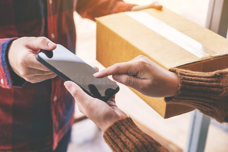 Donna che riceve la scatola del pacchetto e che firma nome sul telefono dal fattorino immagini stock libere da diritti