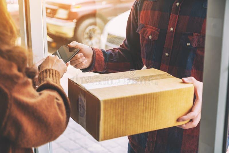 Donna che riceve la scatola del pacchetto e che firma nome sul telefono dal fattorino immagine stock