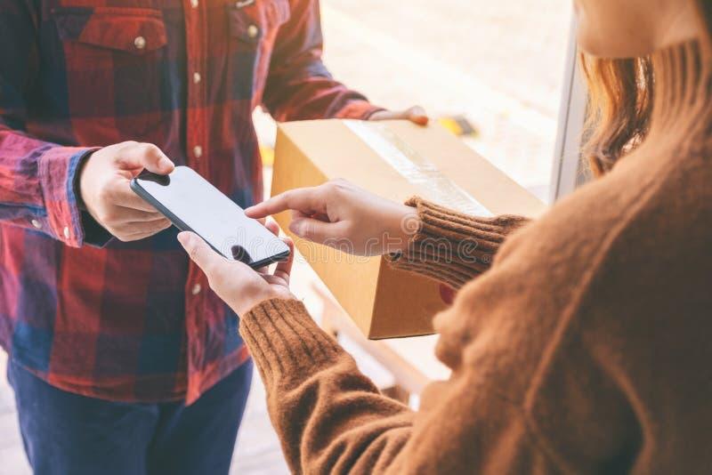 Donna che riceve la scatola del pacchetto e che firma nome sul telefono dal fattorino fotografie stock libere da diritti