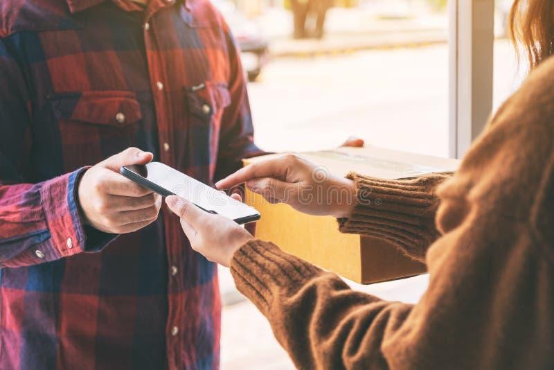 Donna che riceve la scatola del pacchetto e che firma nome sul telefono dal fattorino fotografie stock