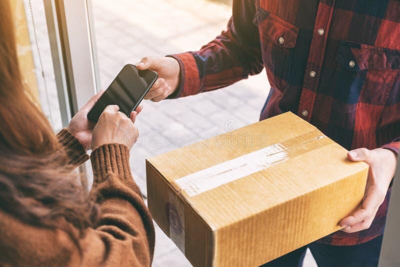Donna che riceve la scatola del pacchetto e che firma nome sul telefono dal fattorino fotografia stock libera da diritti