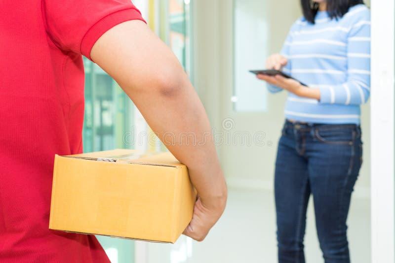 Donna che riceve pacchetto e che firma sulla compressa digitale dal deliv fotografia stock