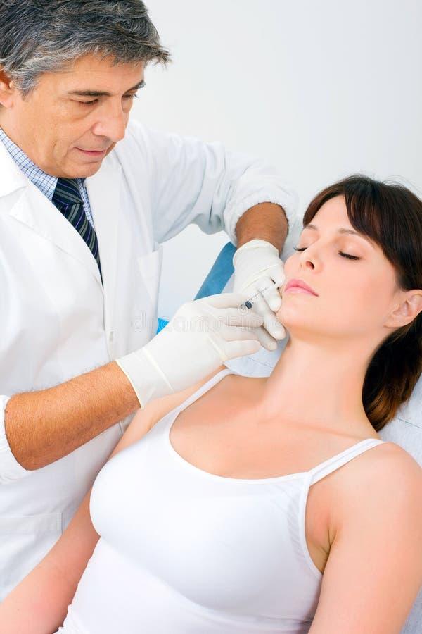 Donna che riceve un'iniezione di botox da un docto fotografie stock libere da diritti
