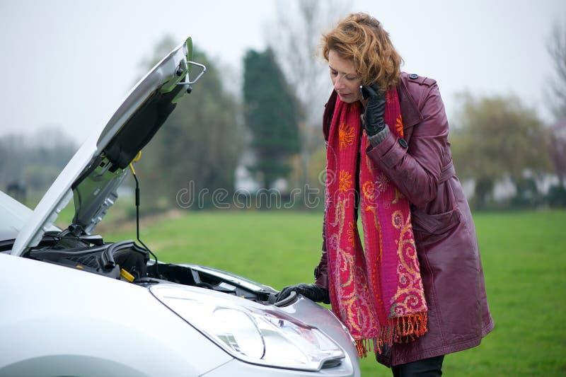 Donna che richiede l'assistenza dell'automobile immagine stock libera da diritti