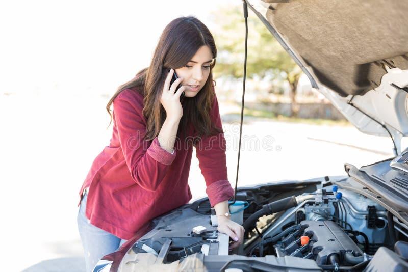 Donna che richiede l'assistenza vicino all'automobile di ripartizione fotografia stock libera da diritti