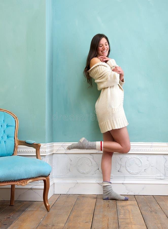 Donna che ride all'interno con il maglione ed i calzini fotografia stock libera da diritti