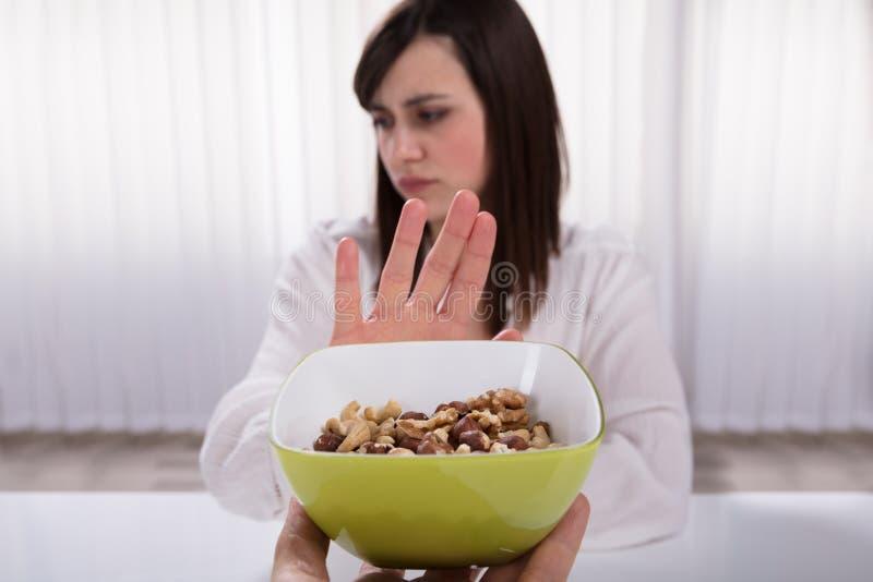 Donna che rifiuta l'alimento del dado immagini stock