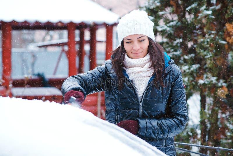 Donna che rimuove neve dall'automobile Neve di pulizia dell'uomo dal parabrezza dell'automobile con la spazzola, fine su Tempo di immagini stock