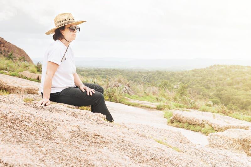 Donna che riposa felicemente su un Outcropping della roccia immagini stock