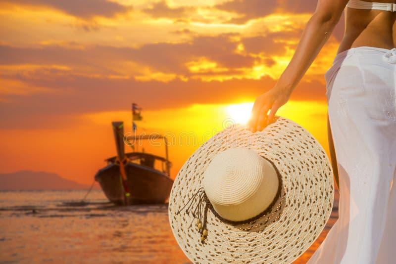 Donna che riposa sulla spiaggia al tramonto che porta un sarong bianco e fotografie stock libere da diritti