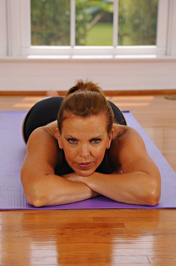 Donna che riposa sulla stuoia di yoga fotografia stock