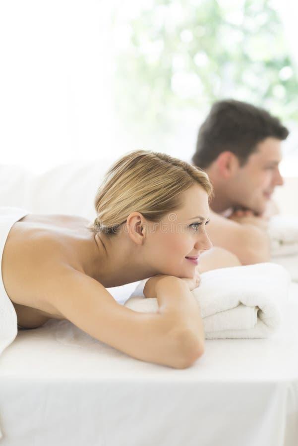 Donna che riposa sulla Tabella di massaggio alla stazione termale fotografia stock