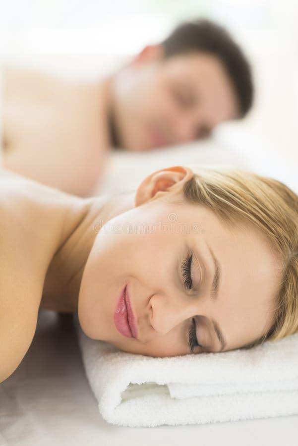 Donna che riposa sulla Tabella di massaggio alla stazione termale immagini stock