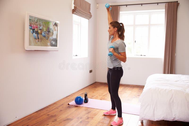 Donna che risolve al DVD di forma fisica sulla TV in camera da letto fotografia stock libera da diritti