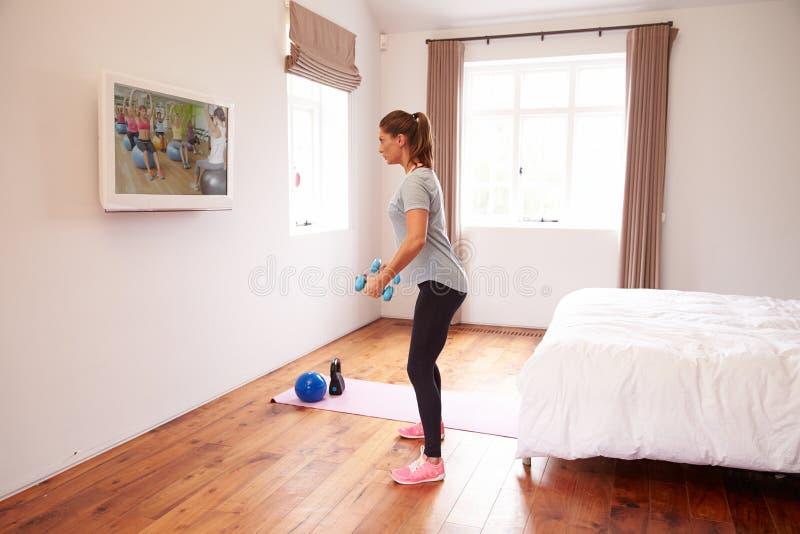 Donna che risolve al DVD di forma fisica sulla TV in camera da letto fotografie stock