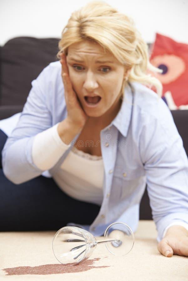 Donna che rovescia casualmente vino rosso su tappeto a casa fotografie stock