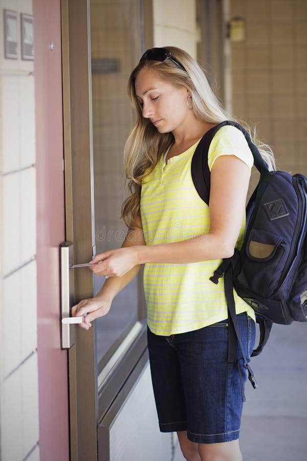 Donna che sblocca la sua porta della camera di albergo immagine stock