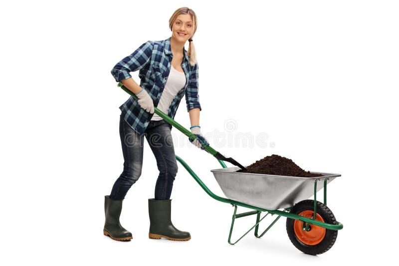 Donna che scarica sporcizia da una carriola fotografie stock