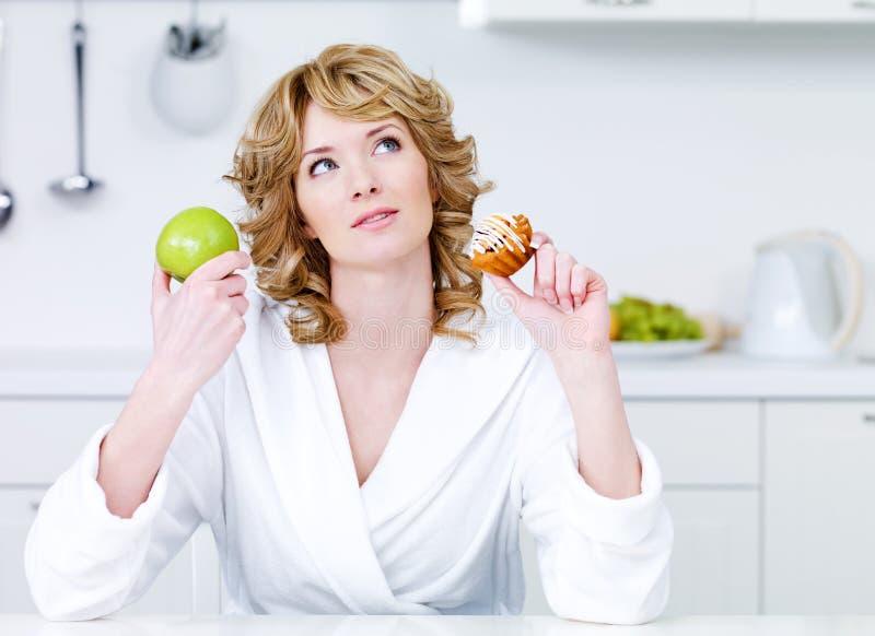 Donna che sceglie fra l'alimento e la torta sani fotografia stock