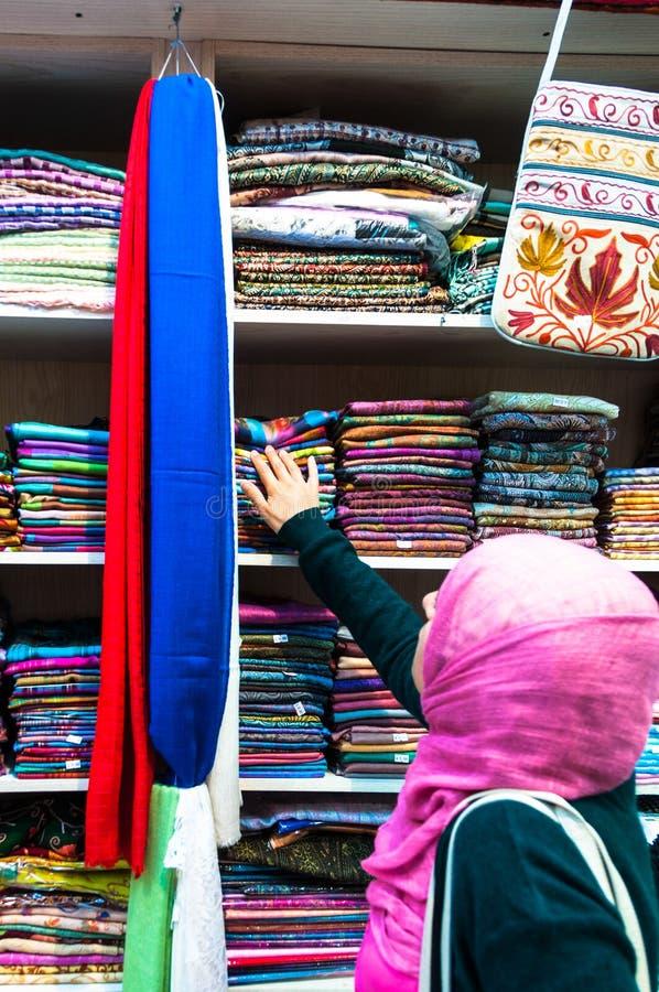 Donna che sceglie i tessuti in Muttrah Souk, Muscat, Oman Medio Oriente immagini stock libere da diritti