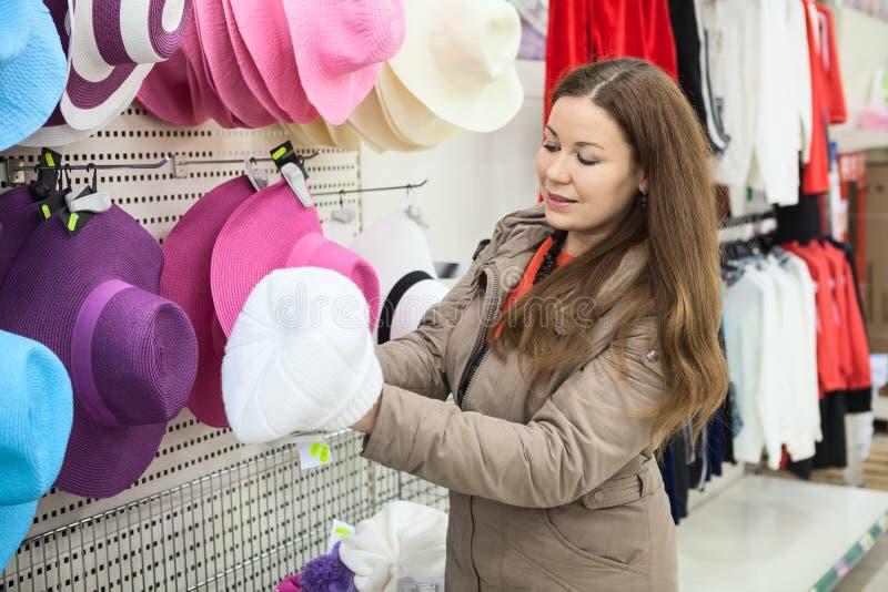 Donna che sceglie il cappello di inverno nel centro del negozio immagine stock libera da diritti