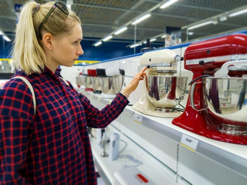 Donna che sceglie il nuovo miscelatore della cucina nel deposito di elettrodomestici fotografia stock libera da diritti