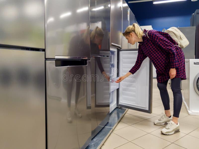 donna che sceglie nuovo frigorifero nel deposito di elettrodomestici fotografie stock