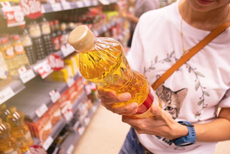Donna che sceglie prodotto in un supermercato acquisto della donna nelle informazioni di prodotto della lettura e del supermercat fotografie stock