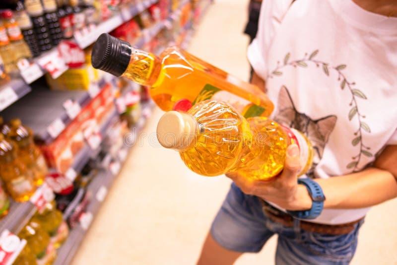 Donna che sceglie prodotto in un supermercato acquisto della donna nelle informazioni di prodotto della lettura e del supermercat fotografie stock libere da diritti