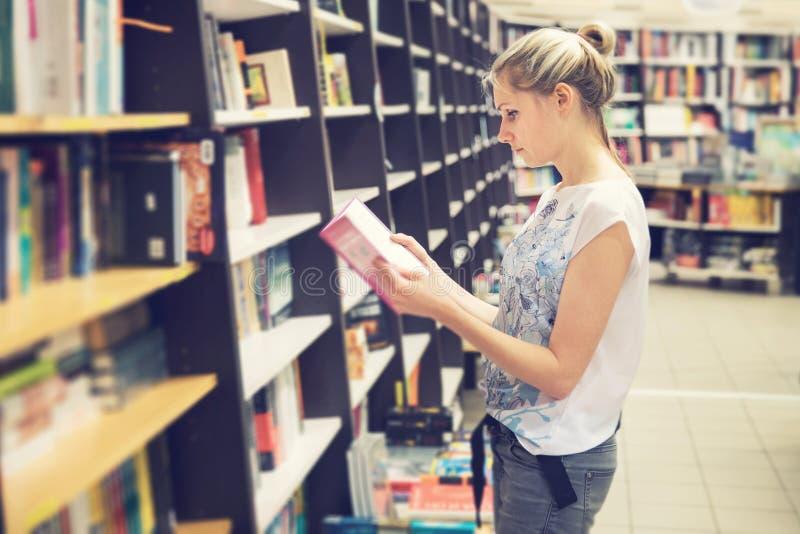 Donna che sceglie un libro per comprare in libreria immagini stock
