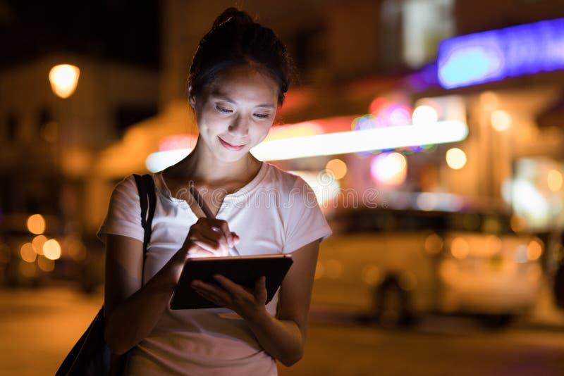Donna che schizza sul computer digitale della compressa alla notte immagini stock