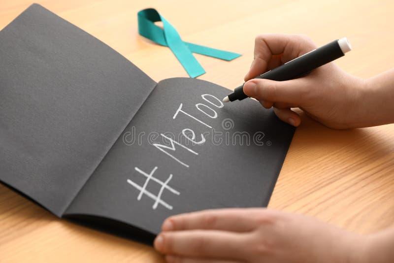 Donna che scrive hashtag MeToo in taccuino vicino al nastro di consapevolezza dell'alzavola alla tavola Aggressione sessuale di a immagini stock libere da diritti