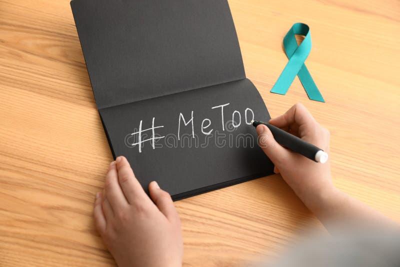Donna che scrive hashtag MeToo in taccuino vicino al nastro di consapevolezza dell'alzavola alla tavola Aggressione sessuale di a immagine stock libera da diritti
