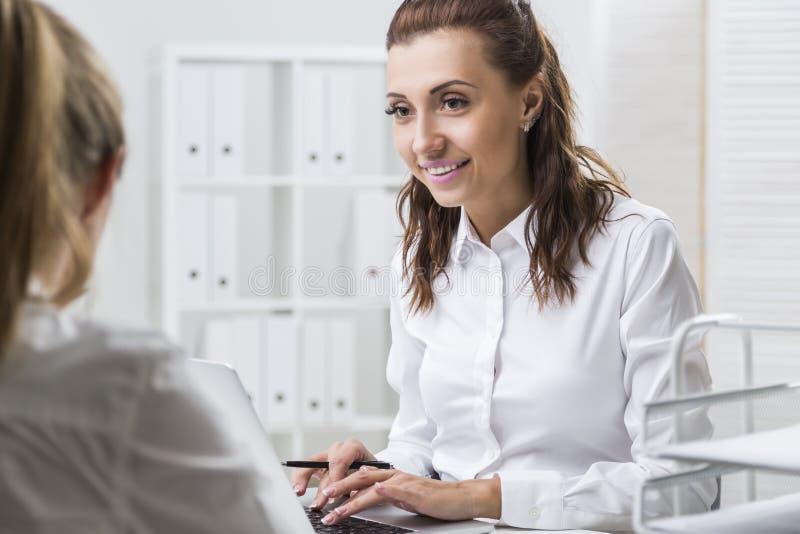 Donna che scrive mentre esaminando il suo collega immagini stock libere da diritti