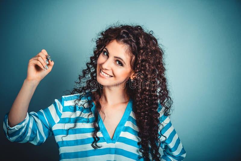 Donna che scrive sorridere della penna di tenuta felice fotografia stock