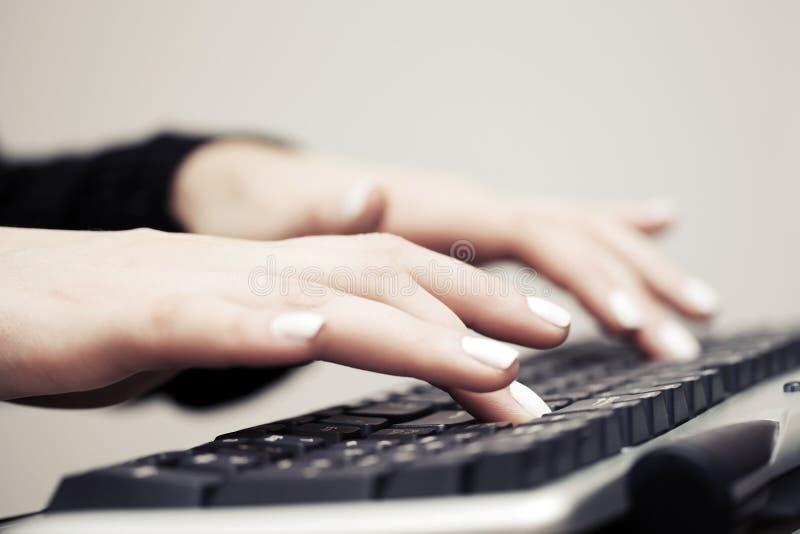 Donna che scrive sulla tastiera di computer fotografie stock