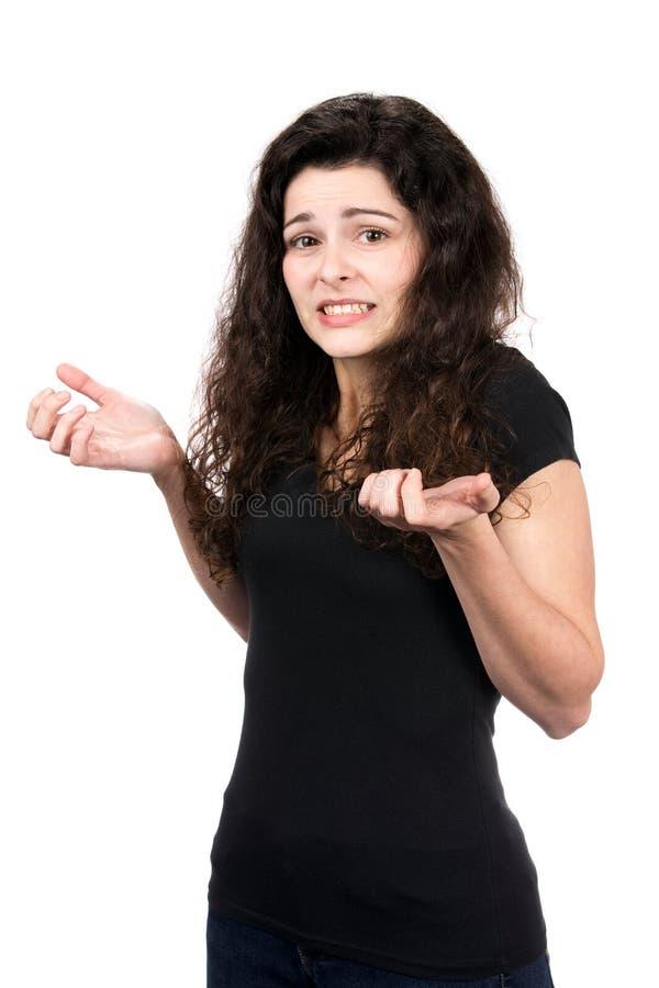 Donna che scrolla le spalle con l'indecisione immagine stock