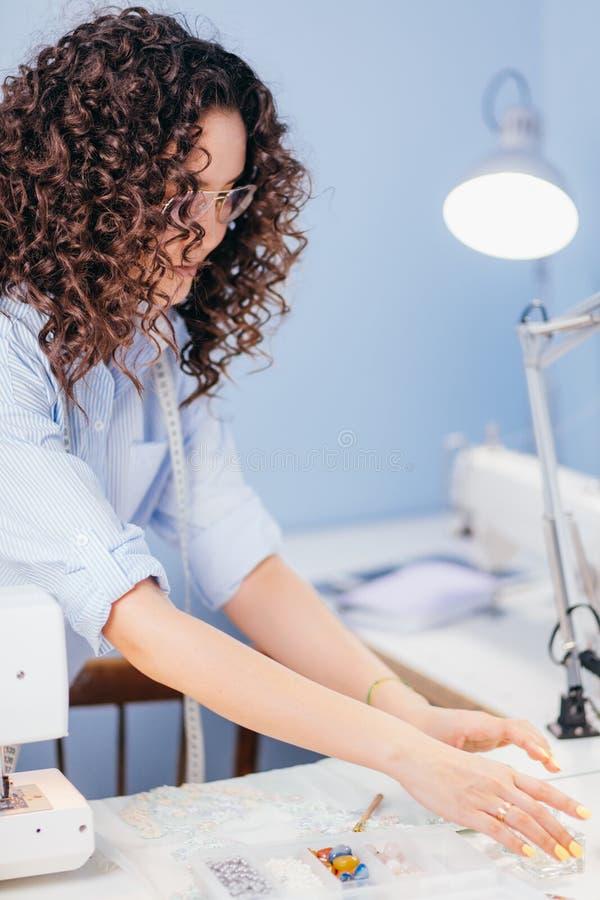Donna che seleziona le perle per i clothers di decorazione allo studio di cucito fotografia stock