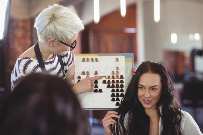 Donna che seleziona un colore dei capelli con lo stilista immagini stock libere da diritti