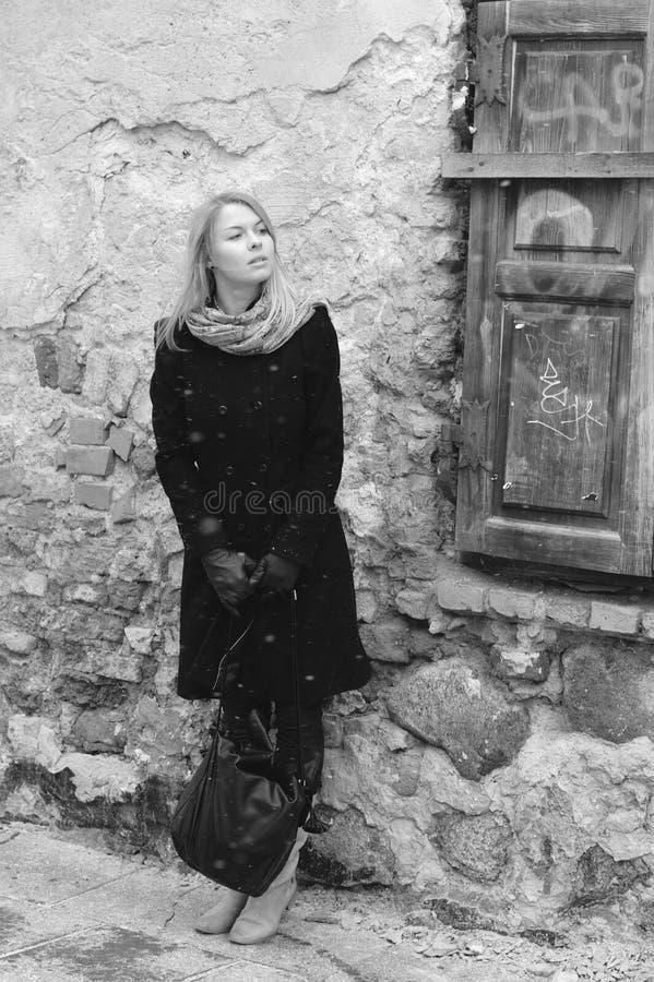 Donna che sembra attendente vicino alla retro parete immagine stock libera da diritti