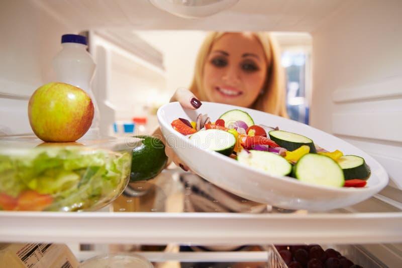 Donna che sembra frigorifero interno in pieno di alimento e che sceglie insalata fotografie stock